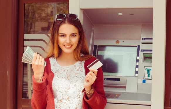 Woman in front of ATM holding cash and card